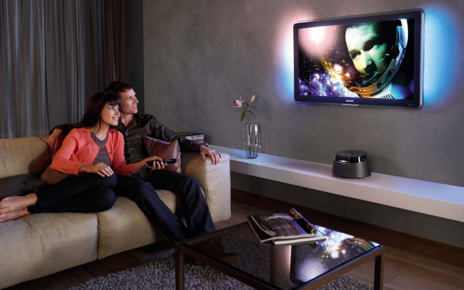 Мужчина и женщина сидят на диване и смотрят телевизор