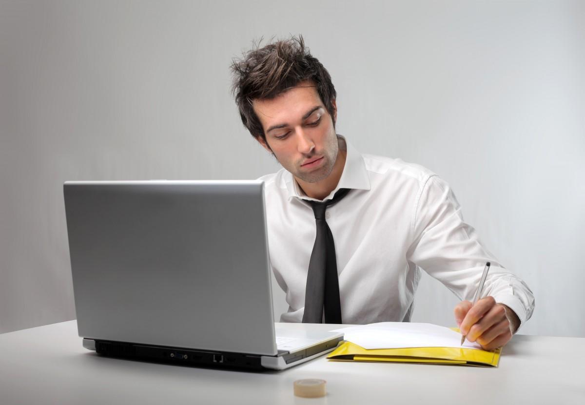 Парень сидит за столом с ноутбуком и пишет на бумаге