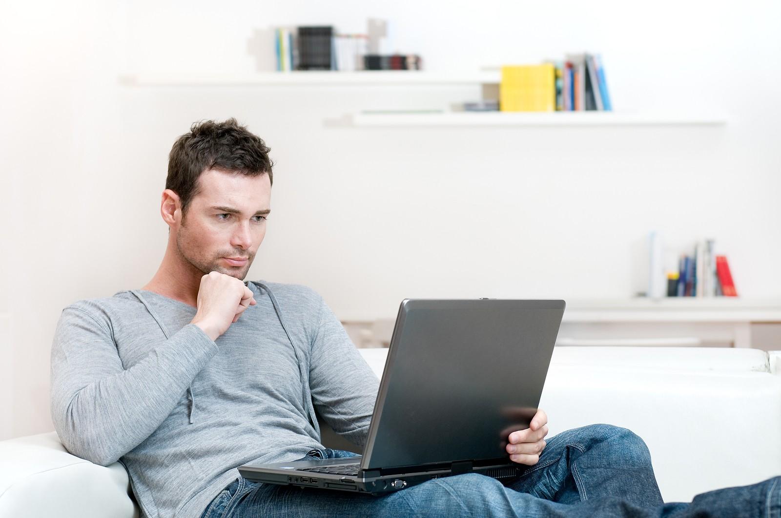 Мужчина с ноутбуком сидит на диване
