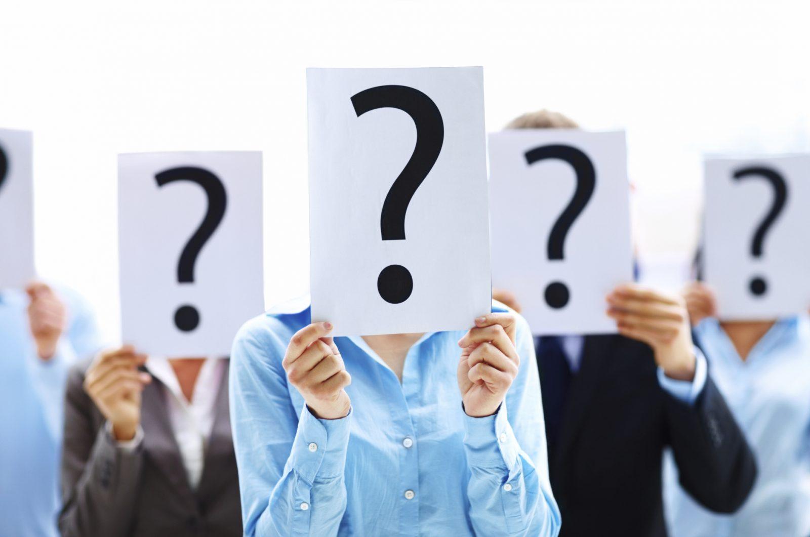 Люди держат в руках листы с изображением знака вопроса