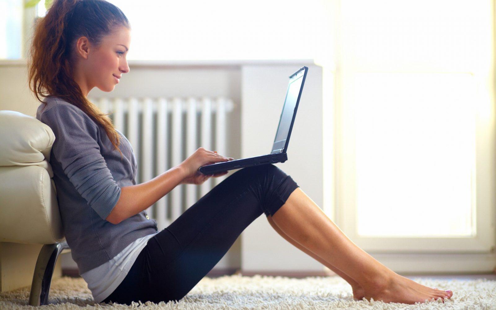 Девушка с ноутбуком сидит на полу