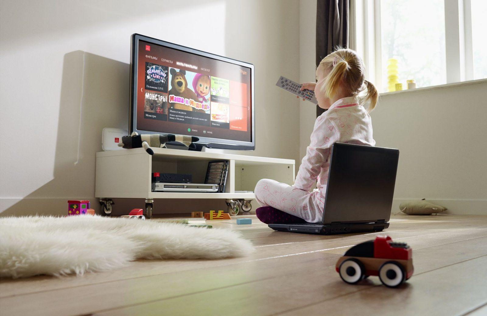 Маленькая девочка смотрит мультики по телевизору