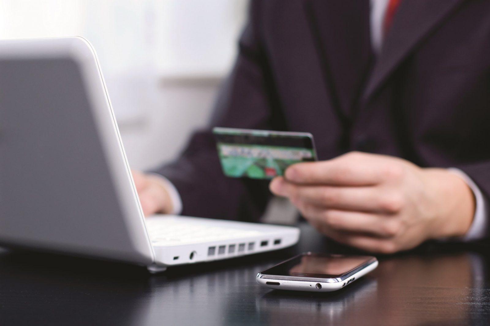 Мужчина за ноутбуком держит банковскую карту