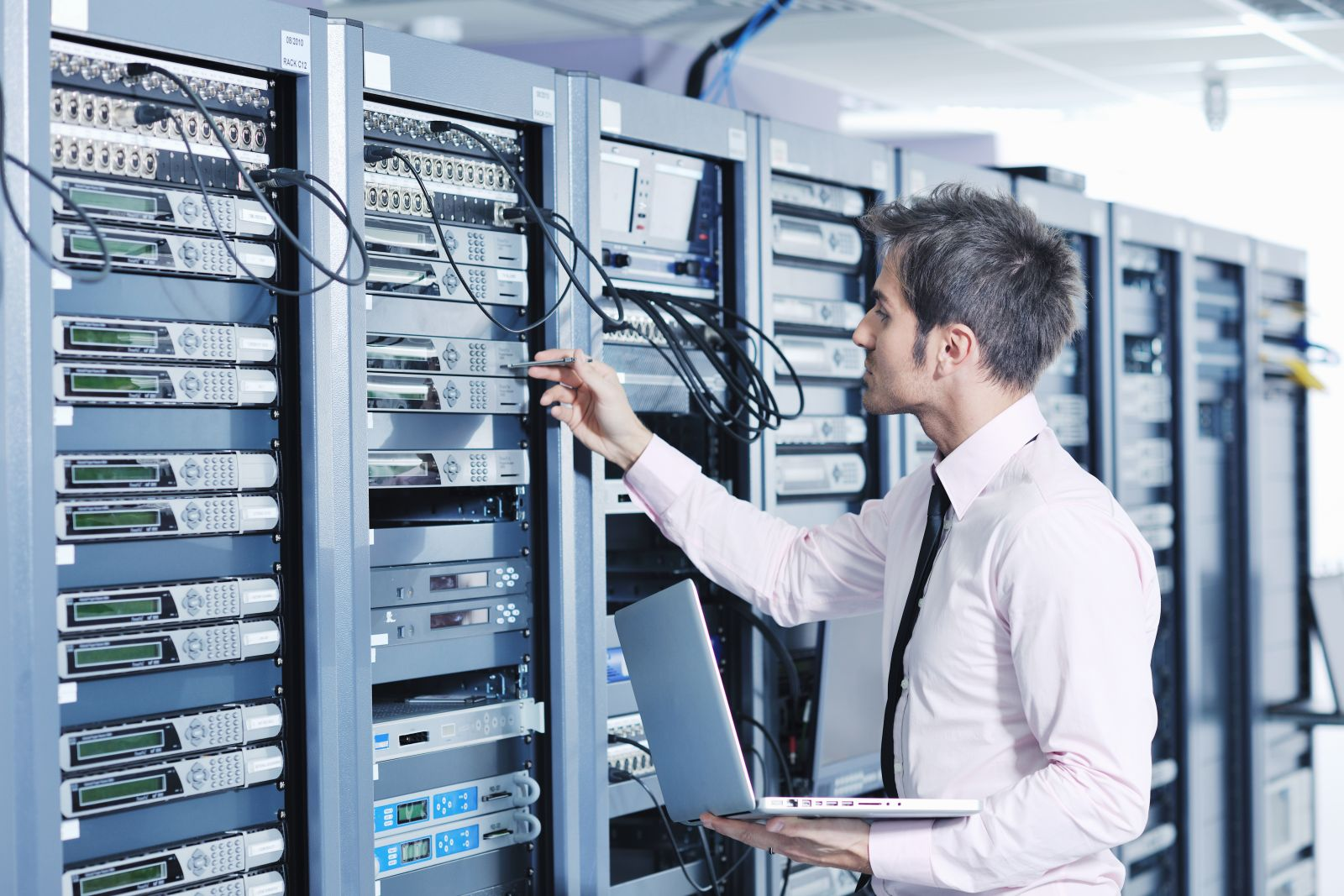 IT-специалист с ноутбуком в руке проверяет сервер