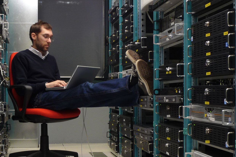 IT-специалист с ноутбуком сидит в серверной