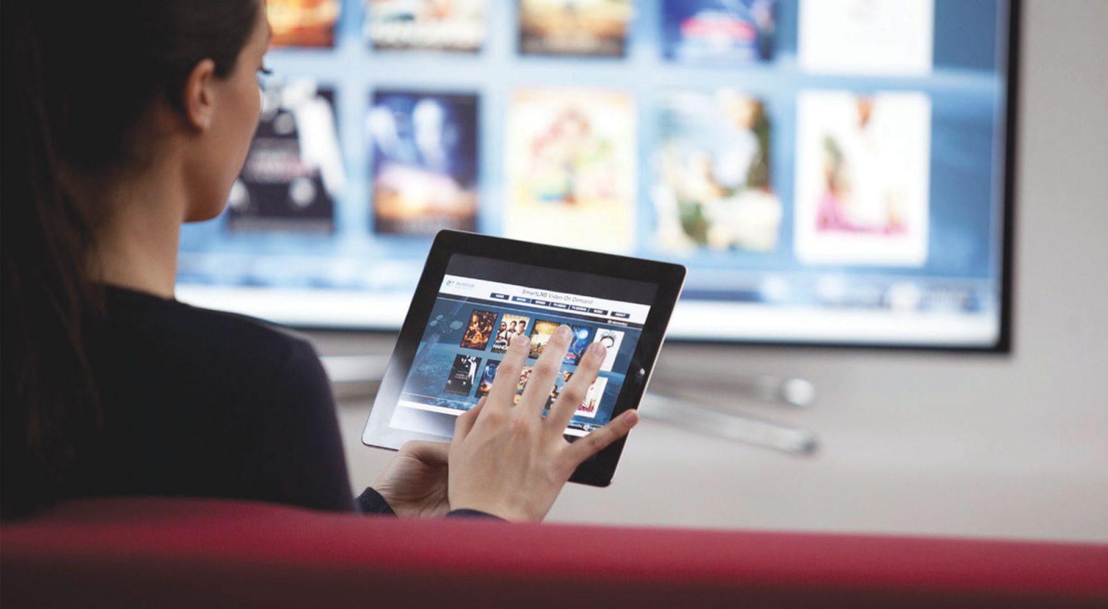 Девушка выбирает фильмы на планшете