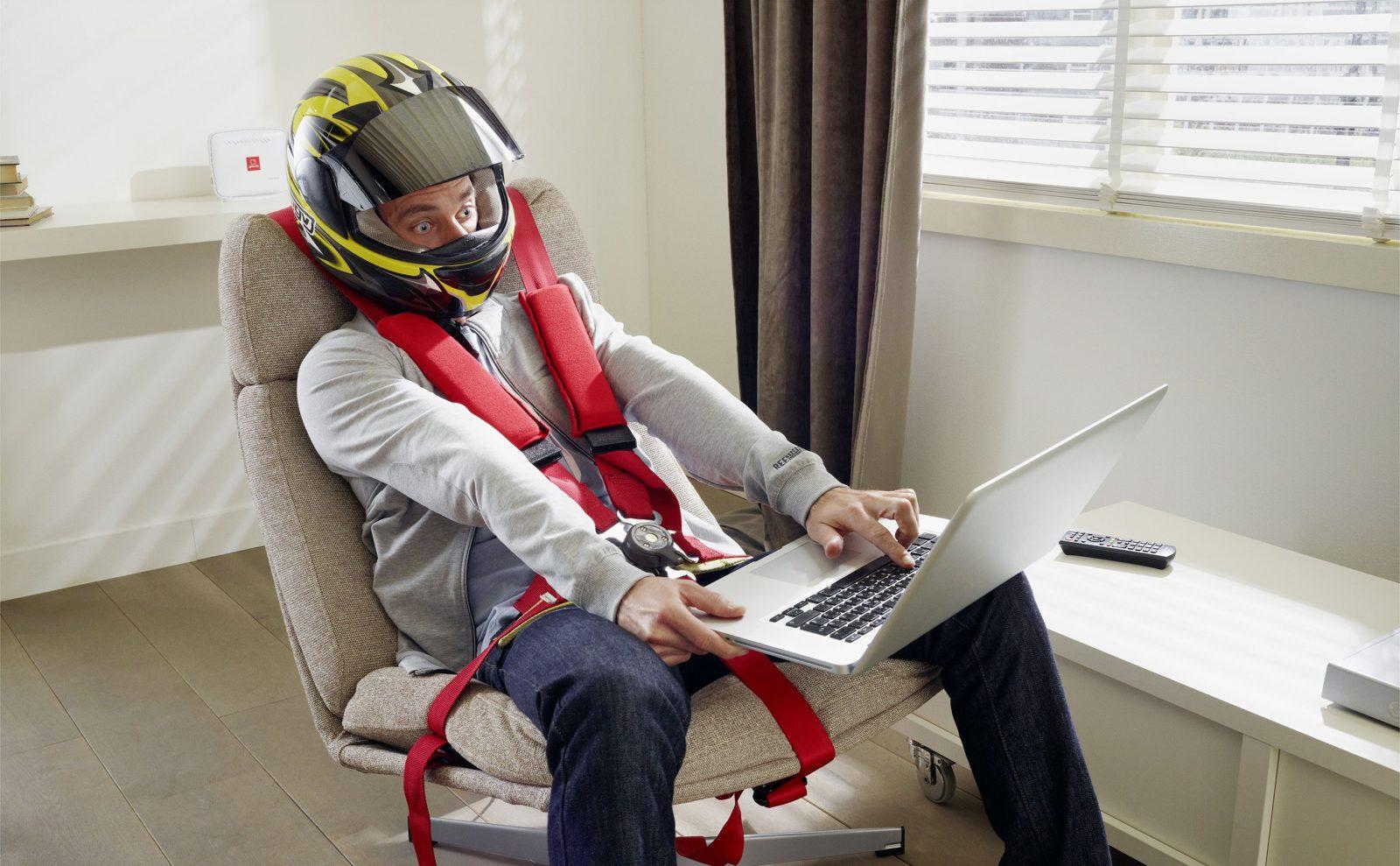 Мужчина в гоночной экипировки сидит в кресле с ноутбуком