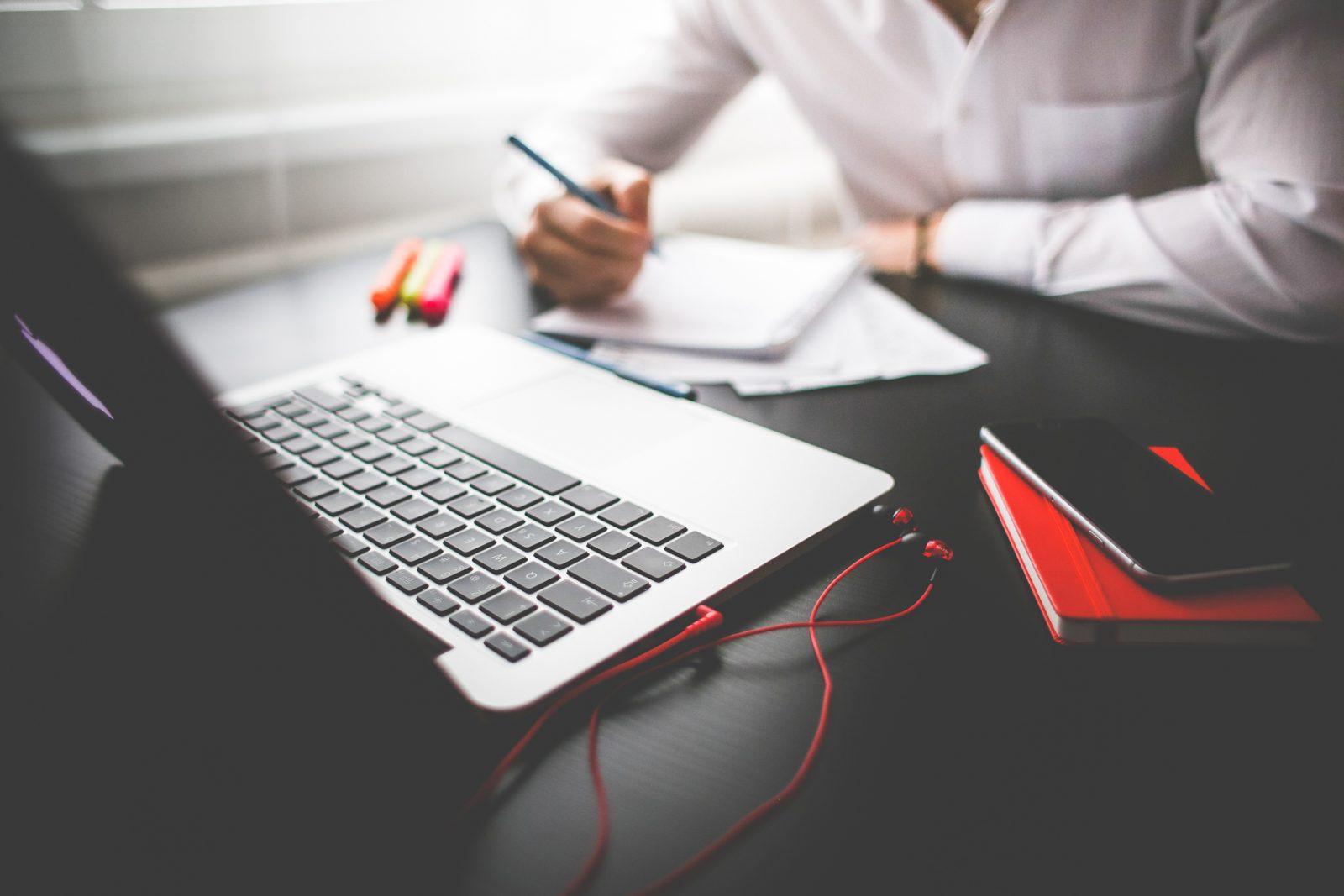 Мужчина сидит за столом с ноутбуком