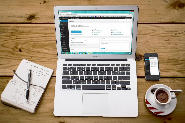 Нетбук, записная книжка, чайная чашка и смартфон на столе